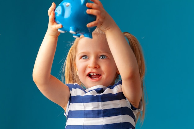 Little girl with piggy bank money box