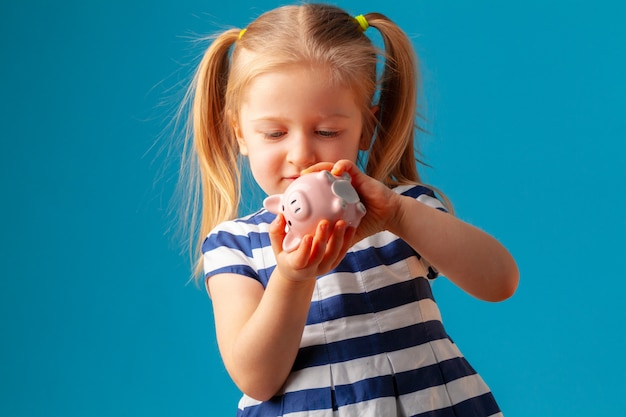 Little girl with piggy bank