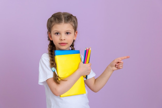 A little girl with pigtails and books for reading and studying points to the side.