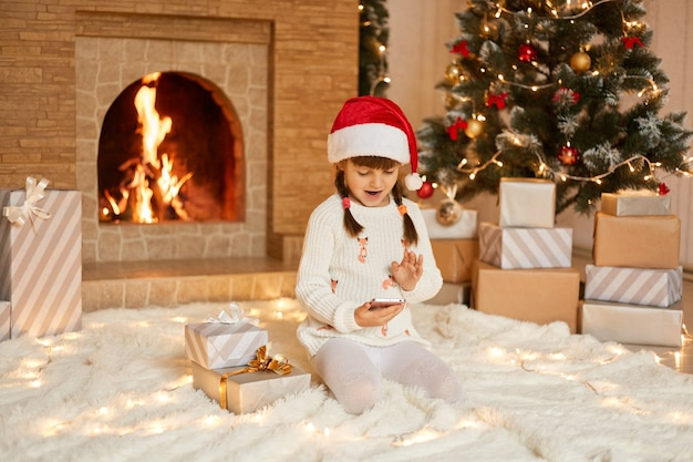 땋은 머리를 가진 어린 소녀는 전화로 친척들과 대화를 나누고 선물에 대해 감사하며 스마트 폰 카메라에 손을 흔들며 인사하고 흰색 스웨터와 산타 클로스 모자를 쓰고 있습니다.