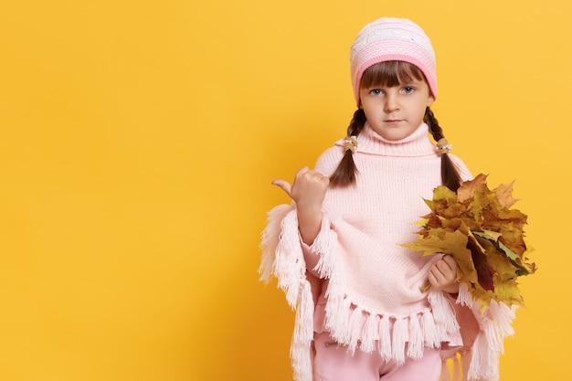 おさげ髪の少女は手に黄色の葉で暖かいピンクのポンチョとキャップをドレスアップ