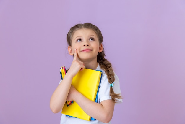 A little girl with pigtails on her head holds several books and pencils.