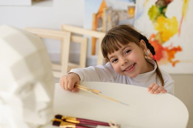 自宅のスタジオ ワーク ショップでおさげ髪の少女は、アート ブラシと笑顔を保持します。