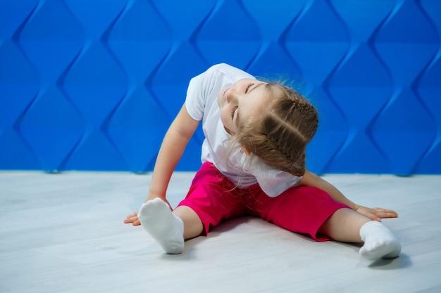 青い背景の上の白いtシャツでおさげ髪の少女。彼女は床の蓮華座に座り、微笑んで手を振る。