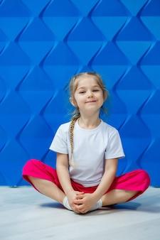 Маленькая девочка с косичками в белой футболке на синем фоне. она сидит на полу в позе лотоса, улыбается и машет руками.