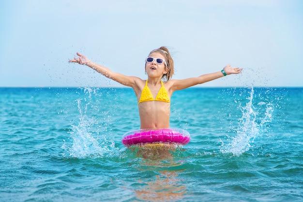 海で膨らませることができるピンクの丸い少女 Premium写真