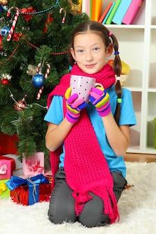 Маленькая девочка с розовым шарфом и чашкой горячего напитка сидит возле елки