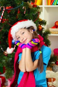 핑크 스카프와 크리스마스 트리 근처에 앉아 여러 가지 빛깔의 장갑 어린 소녀