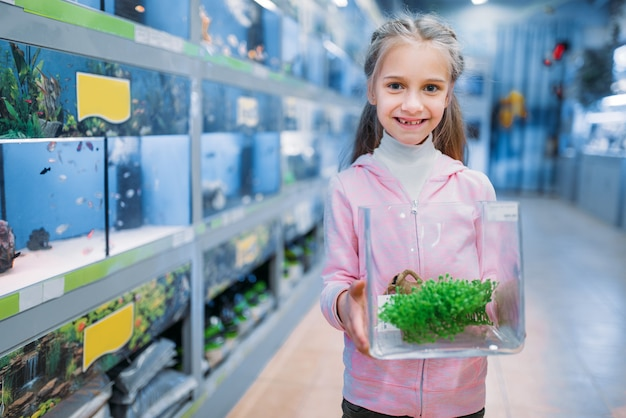 Little girl with plant for aquarium in pet shop. kid chooses element of flora for her fishbowl in petshop