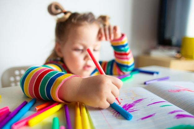 Little girl with a ponytail in a colorful striped jacket drawing
