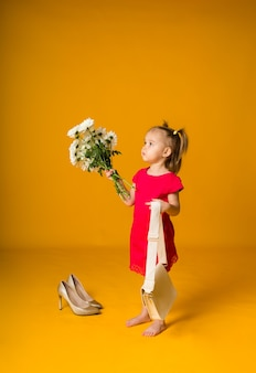 Little girl with ponytails in a red dress stands sideways with a bouquet of white flowers on a yellow surface with space for text