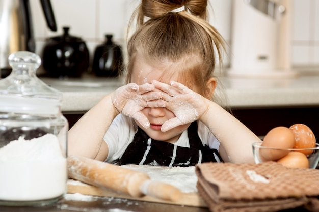Little girl with  preparing bake homemade holiday pie in kitchen.