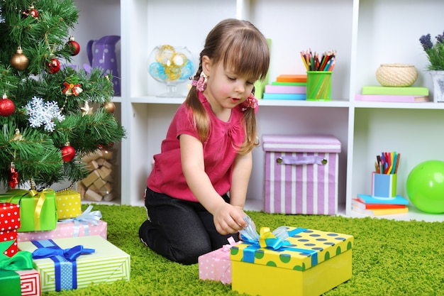 방에 있는 크리스마스 트리 근처에 선물 상자가 있는 어린 소녀