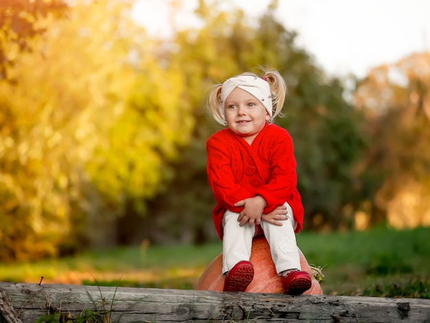 Маленькая девочка с тыквой в осеннем парке