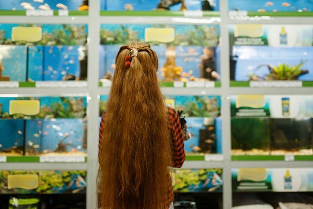 水族館、ペット ショップで魚を見ている子犬を持つ少女。ペットショップで子供を買う道具、家畜のアクセサリー