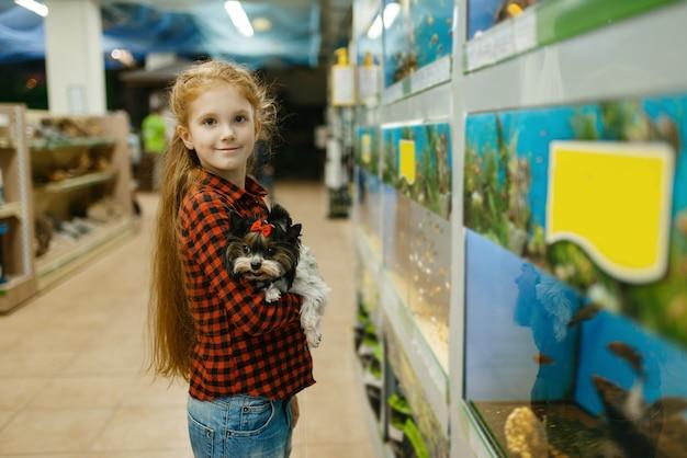 水族館、ペット ショップで魚を見ている子犬を持つ少女。ペットショップで子供が道具を買う