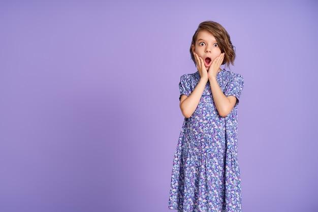 Маленькая девочка с фиолетовым платьем выглядит удивленной на фиолетовом фоне