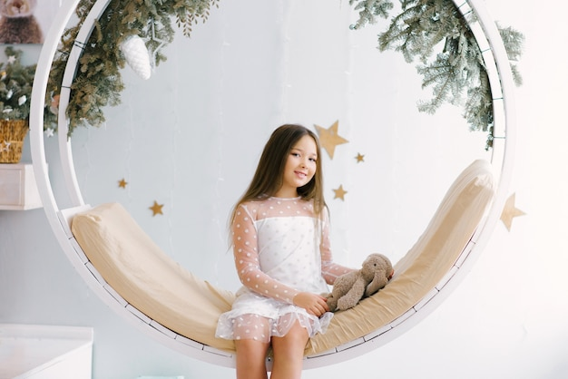 Little girl with rabbit on a christmas swing in the children's room