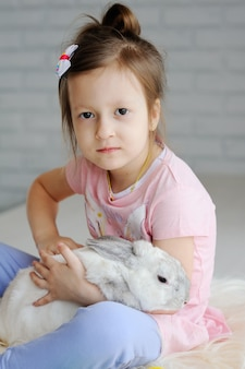 Little girl with a rabbit on a white background