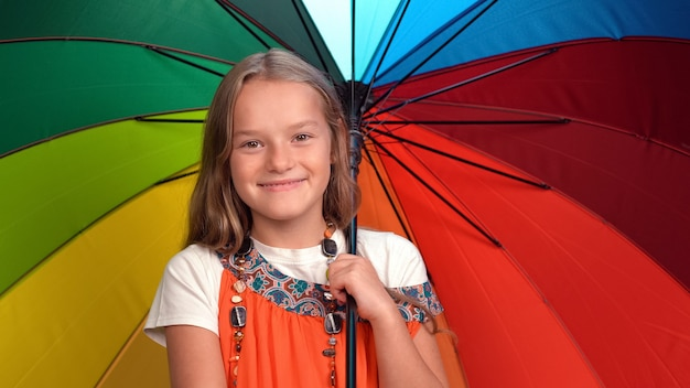 Маленькая девочка с радужным зонтиком в руках в оранжевом платье стоит счастливая