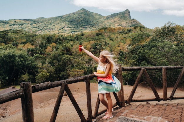 A little girl with a red can of drink in her hands against the background of the mountains of the island of mauritius, nature reserve, chamarel sands.mauritius island.