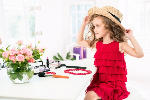 A little girl with red dress and cosmetics.