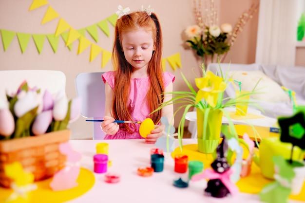 Маленькая девочка с рыжими волосами раскрашивает желтое яйцо на поверхность пасхального декора