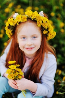 A little girl with red hair smiles against a field of dandelions and green grass.