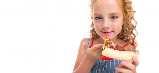 A little girl with red heap hair in a red jersey and blue and white jumpsuit in a stripe eats a big pizza slice