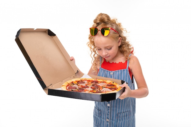 A little girl with red heap hair in a red jersey and blue and white jumpsuit in a stripe holds a large pizza in a box.