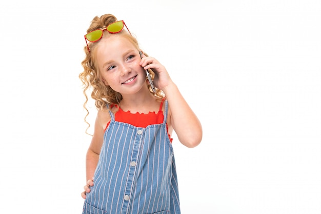A little girl with red heap hair in a red jersey and a blue-and-white stripe jumpsuit speaks on the phone.