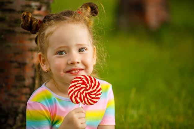 Маленькая девочка с красным леденцом на палочке летом в парке.