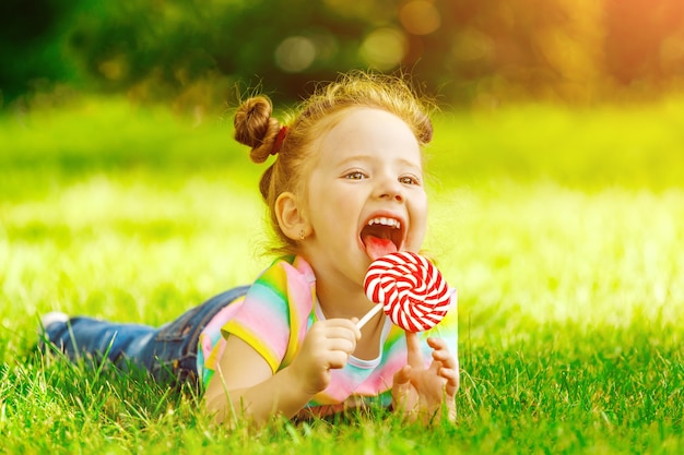 A little girl with a red lollipop lies on the summer grass in the park.