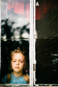 Little girl with sad face looking through window