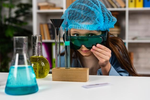 Маленькая девочка в защитных очках и сетке для волос делает научные эксперименты