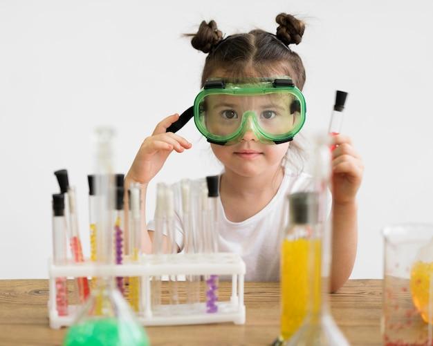 Bambina con gli occhiali di protezione in laboratorio