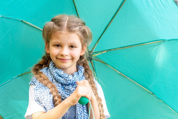 A little girl with a scarf holding an umbrella.