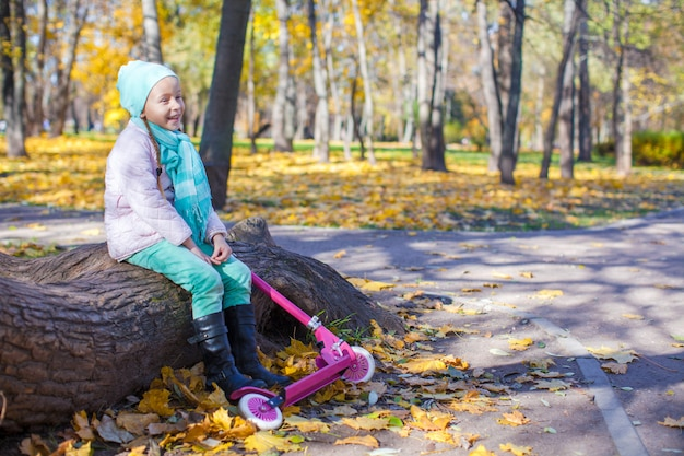 Little girl with scooter in the autumn park