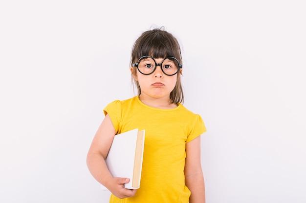Маленькая девочка с серьезным жестом в желтой футболке и круглых черных очках держит белую бумагу в одной руке на белом фоне
