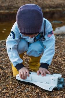 Маленькая девочка с челноком в реке