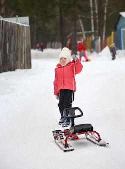 Little girl with sled uphill climbs