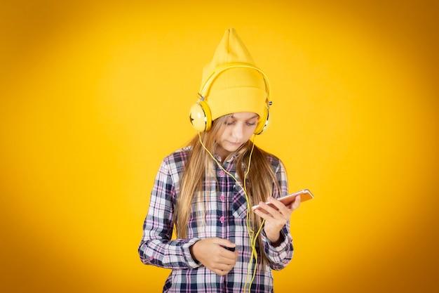 スマートフォンとヘッドフォンの黄色い壁を持つ少女