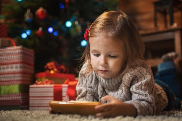 크리스마스 트리, 선물, 크리스마스를 축하하는 촛불을 들고 집에서 스마트폰을 들고 있는 어린 소녀
