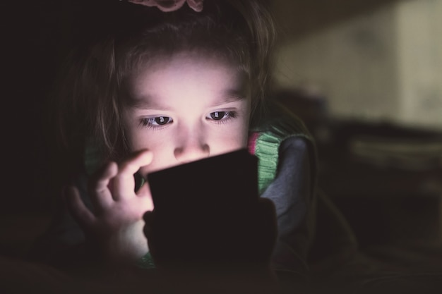 Little girl with smartphone lying in a bed,
