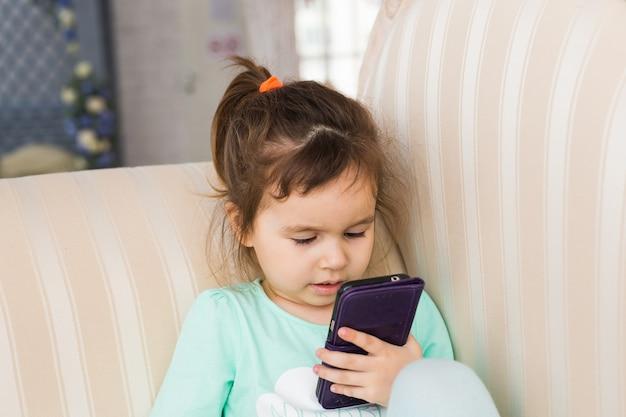 Маленькая девочка со смартфоном, лежа в постели, перед сном