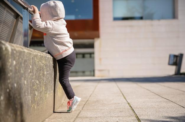 운동화와 후드티를 입은 어린 소녀는 도시 광장에서 금속 난간으로 열심히 훈련합니다
