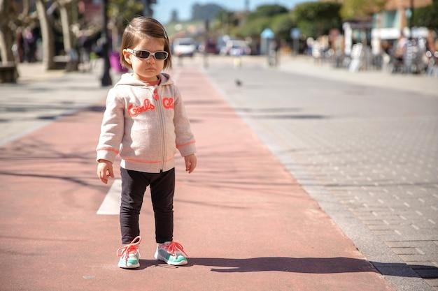 Маленькая девочка в кроссовках и солнцезащитных очках стоит над взлетно-посадочной полосой в солнечный день