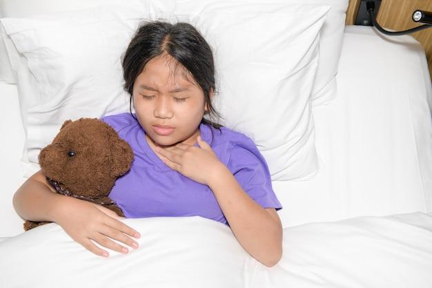 ベッドに横たわっておもちゃのクマの腹を保持している喉の痛みを持つ少女、ヘルスケアの概念