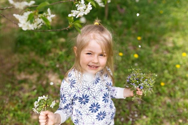 Маленькая девочка с весенними цветами на зеленой лужайке в саду.