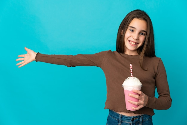 青い背景に分離されたイチゴのミルクセーキを持つ少女は、来て招待するために手を横に伸ばします